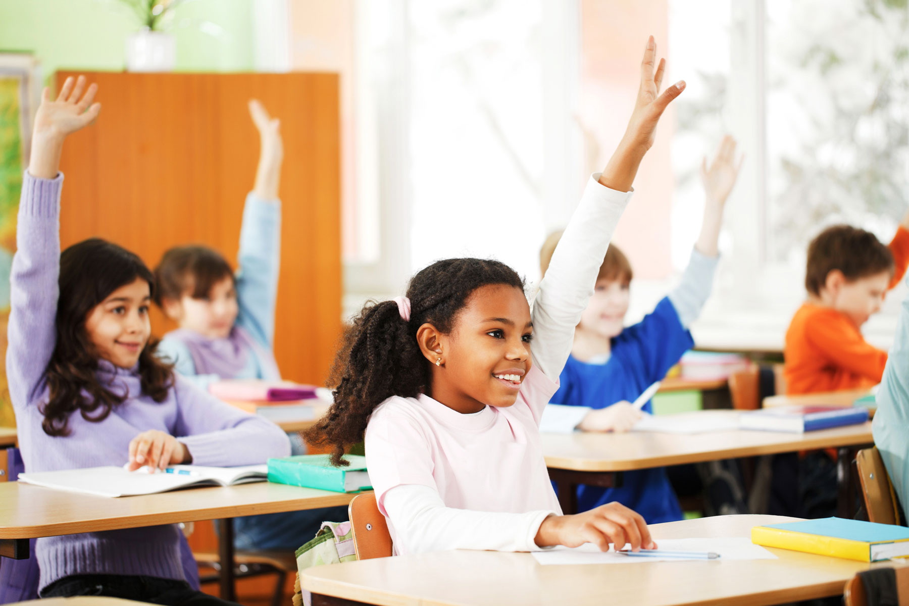 diverse young students in classroom with hands raised to answer question