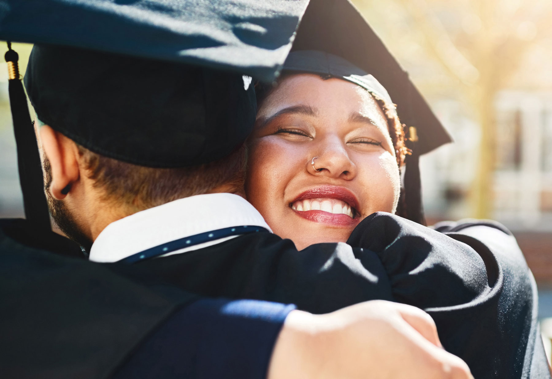 college graduates celebrating in embrace