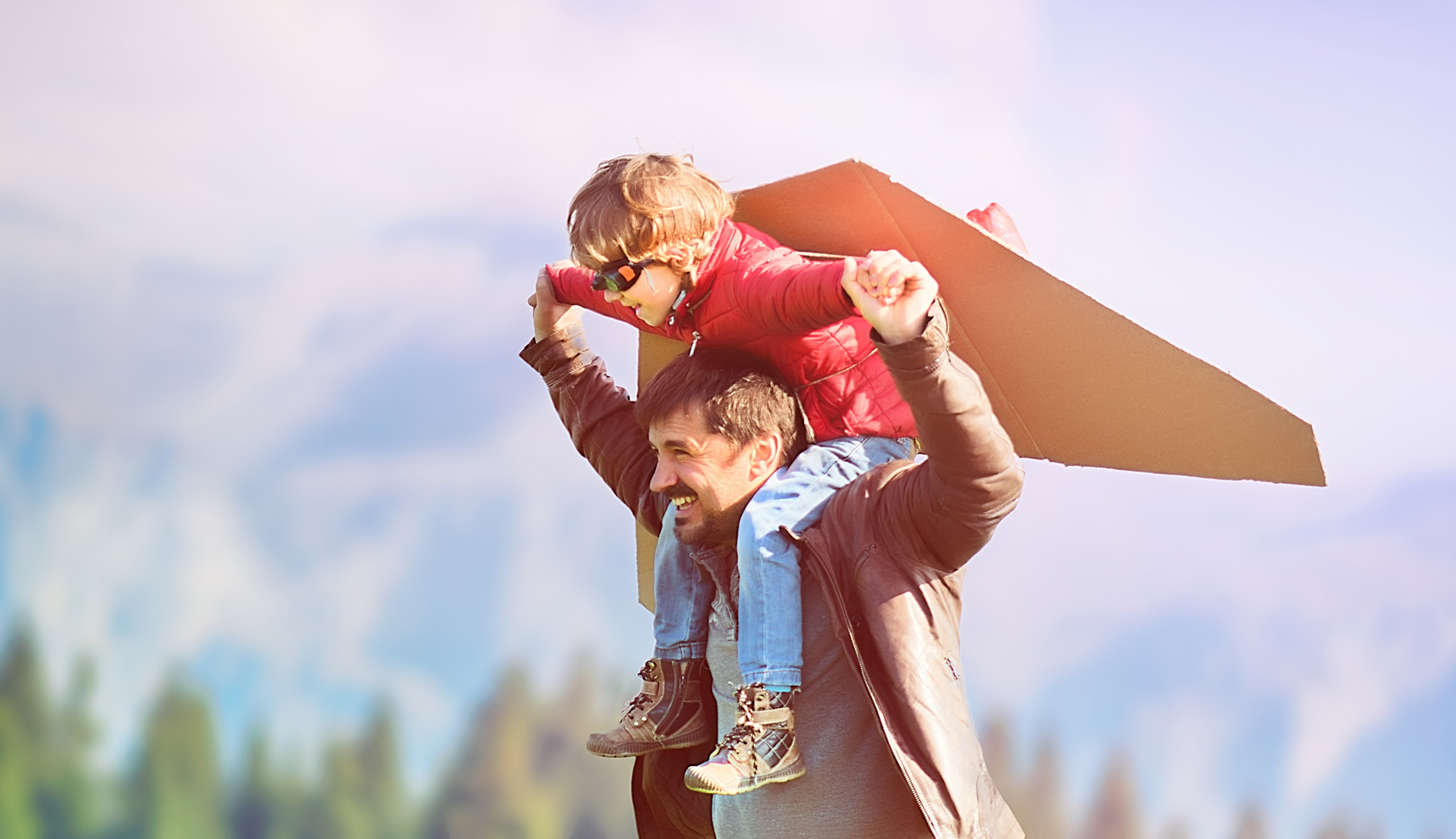 dad with son on his shoulders pretending to fly like an airplane