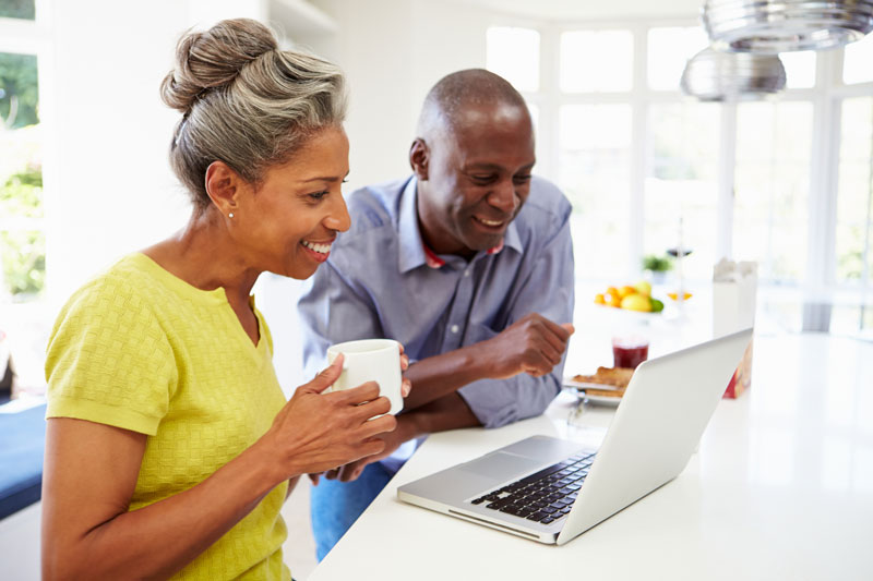 happy couple applying for retirement on laptop in kitchen