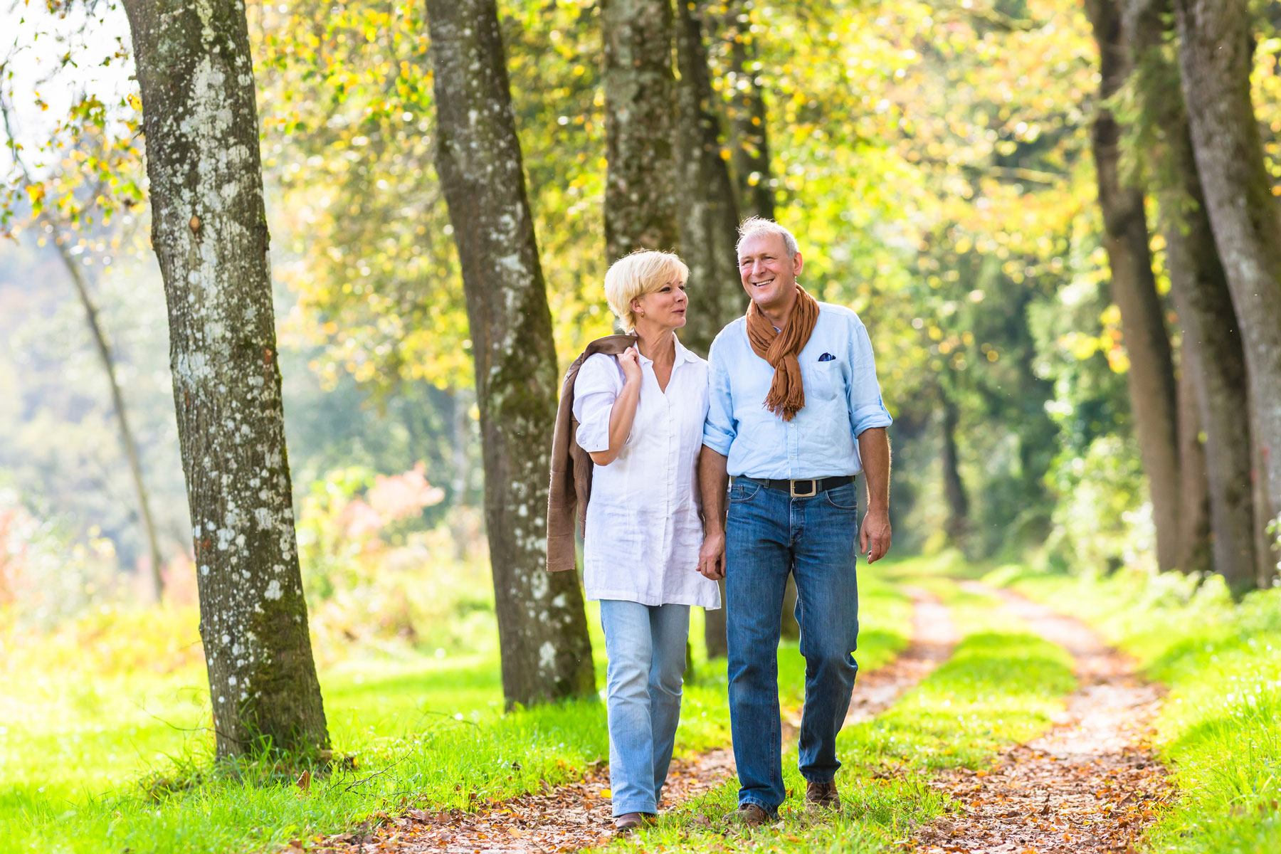 happy retired couple walking on path in woods