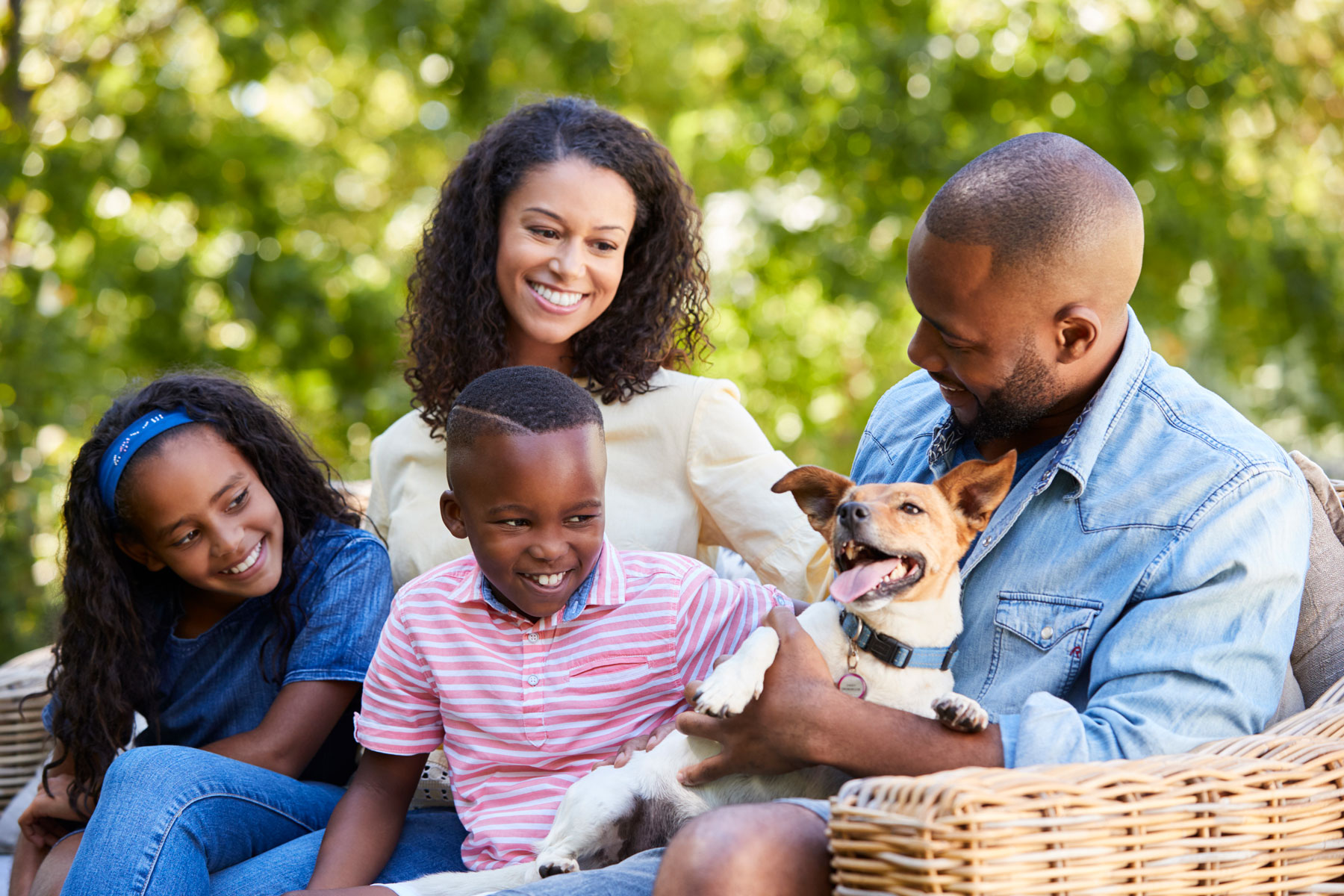 family outdoors with dog, smiling