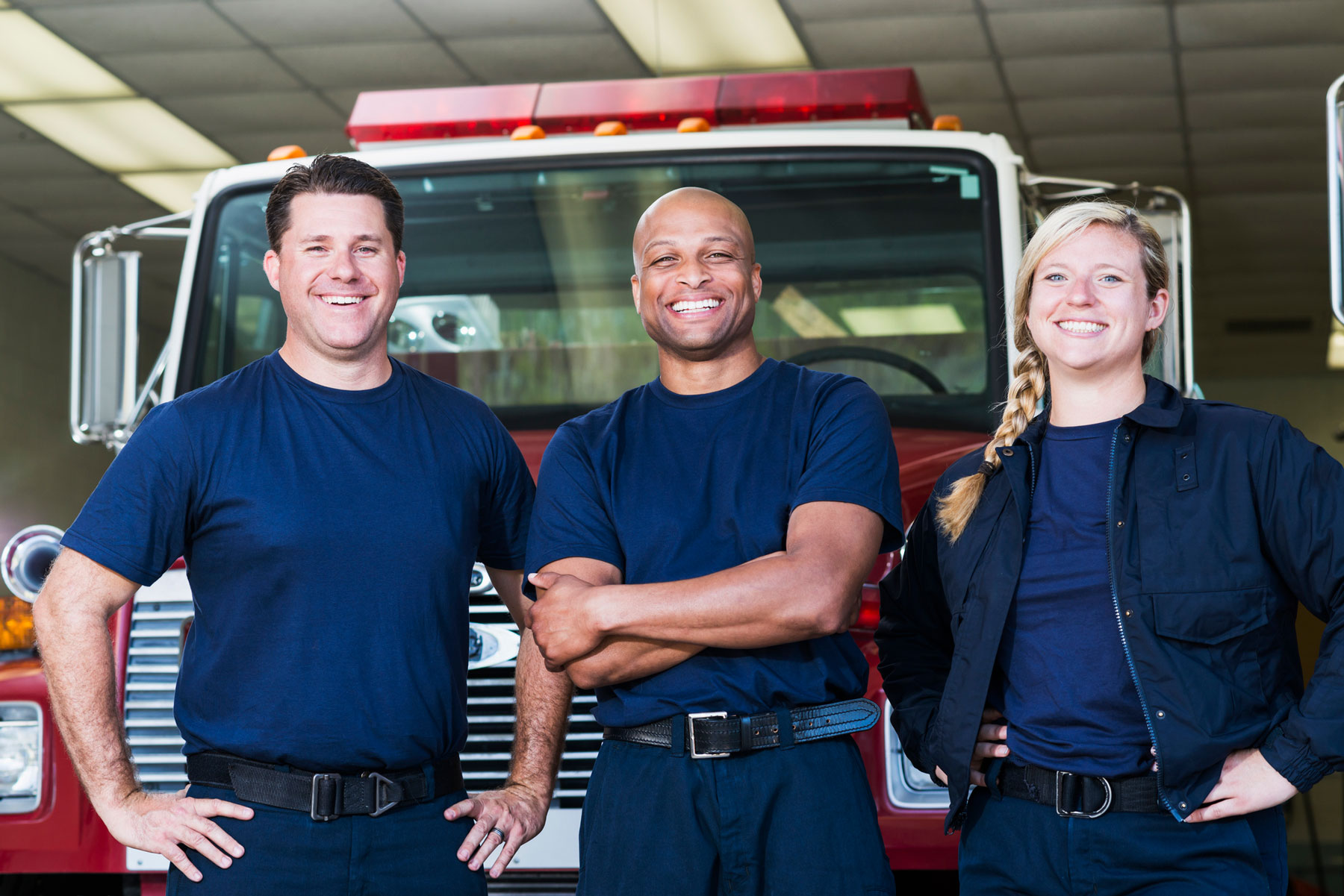 men and women firefighters standing in front of fire truck, smiling