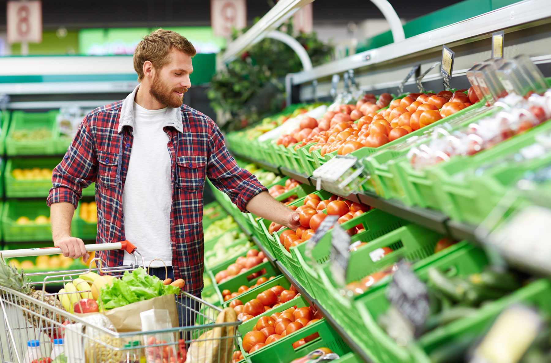 man shopping in produce aisle of grocery store