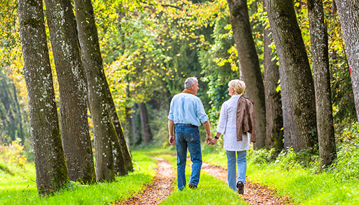 Seniors walking happily along path in woods