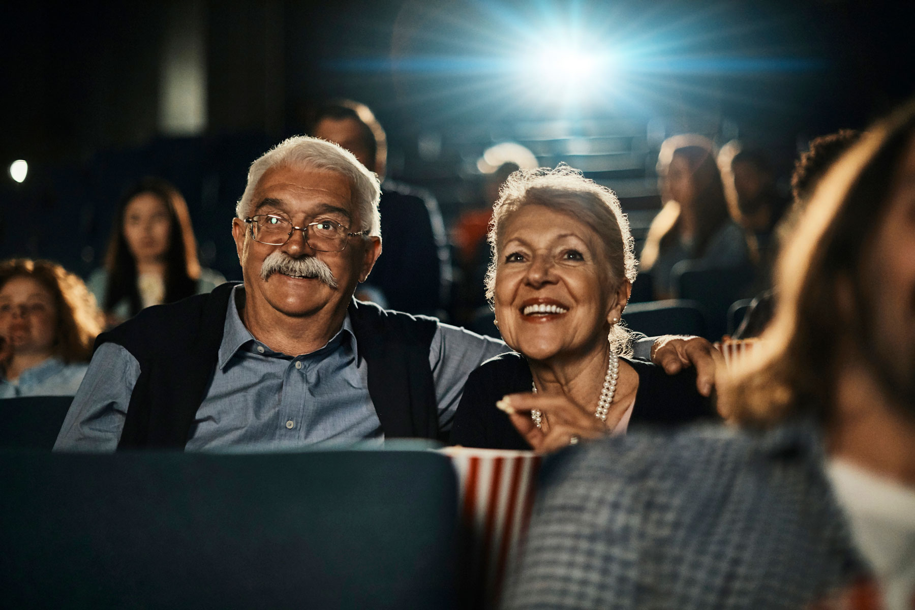 senior couple watching movie inside theatre