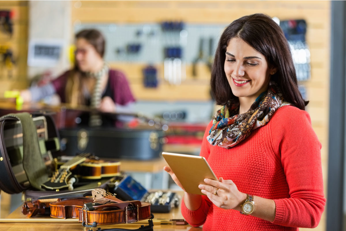 woman in violin store, checking retirement account on tablet device