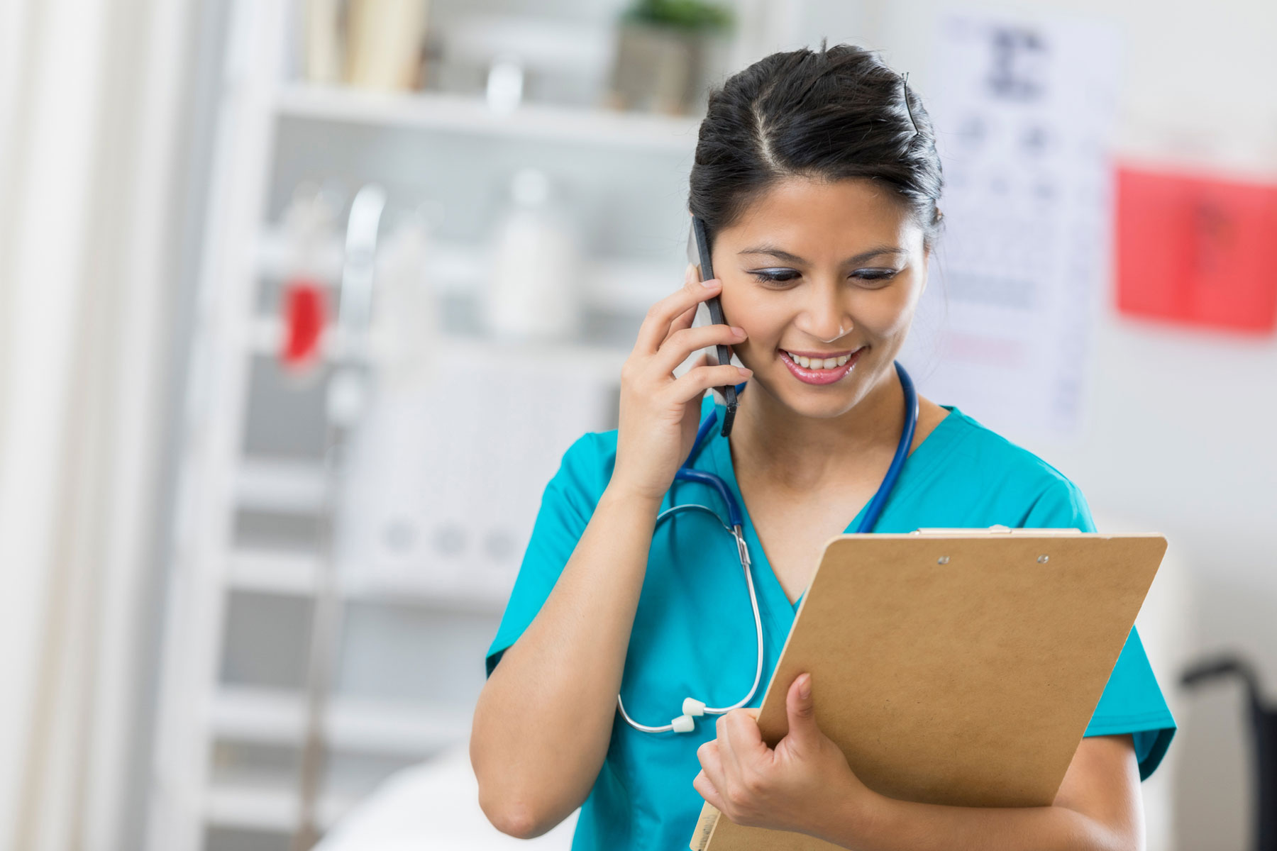 nurse with clipboard on phone
