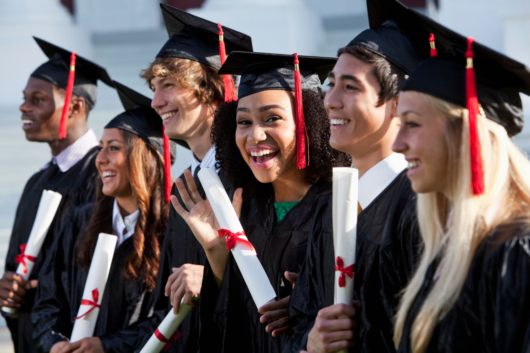 happy, diverse college students at graduation ceremony