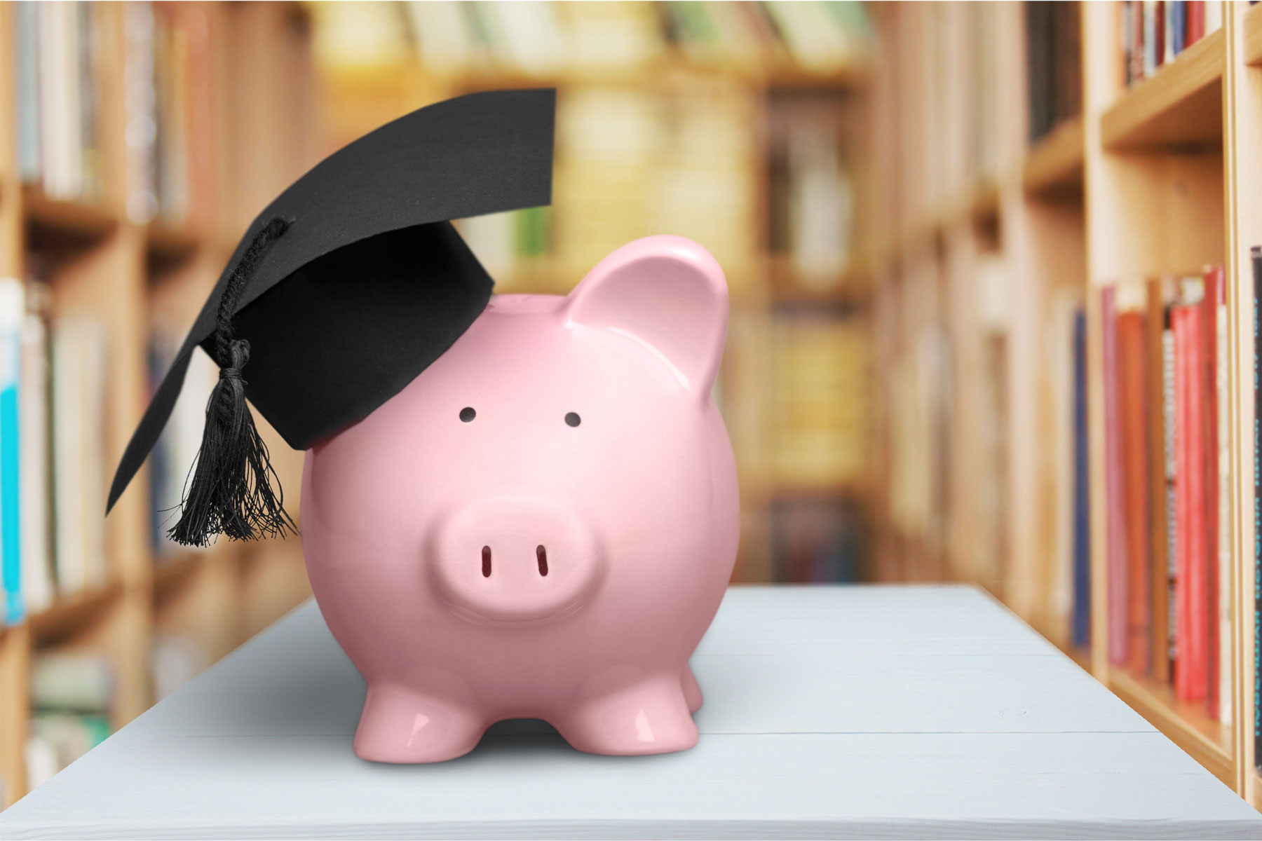 piggy bank with graduation cap in library