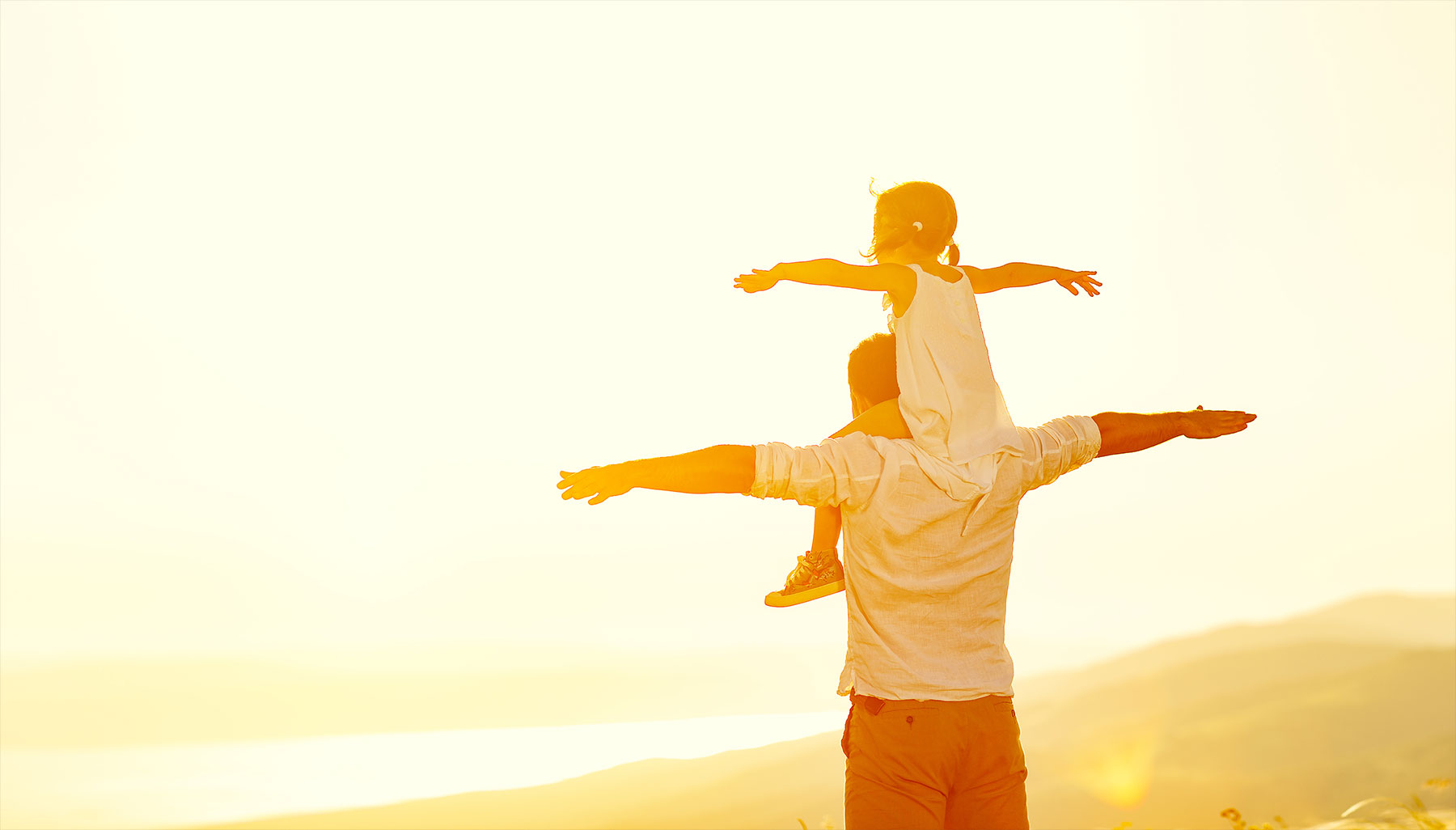 father holding daughter on shoulders, daughter with arms spread in flying motion