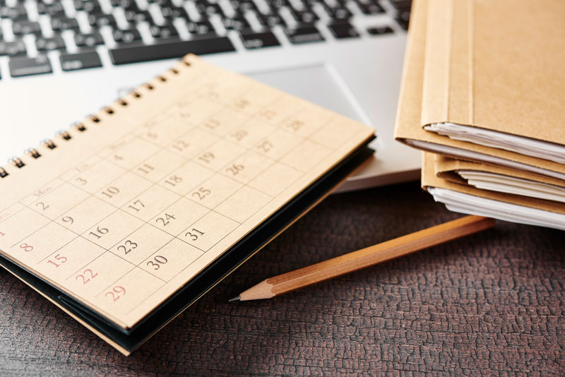 calendar, pencil, laptop, and file folders