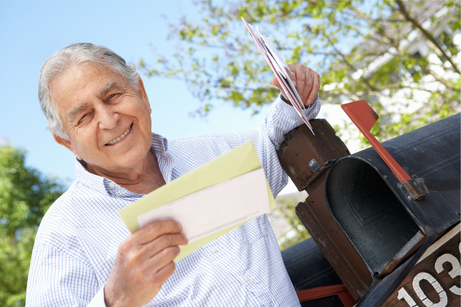 senior male getting unclaimed property check in the mail
